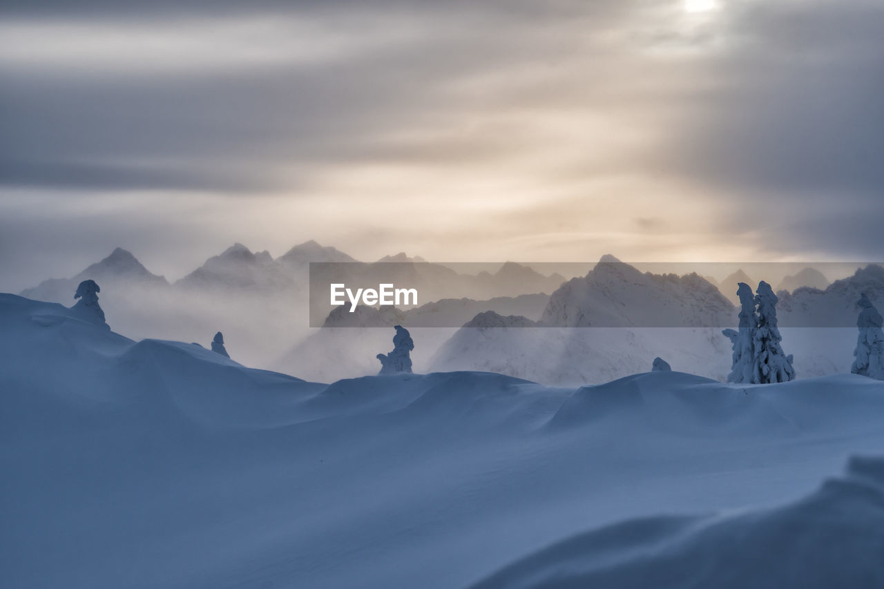 Scenic View Of Snow Covered Landscape Against Cloudy Sky During Sunset