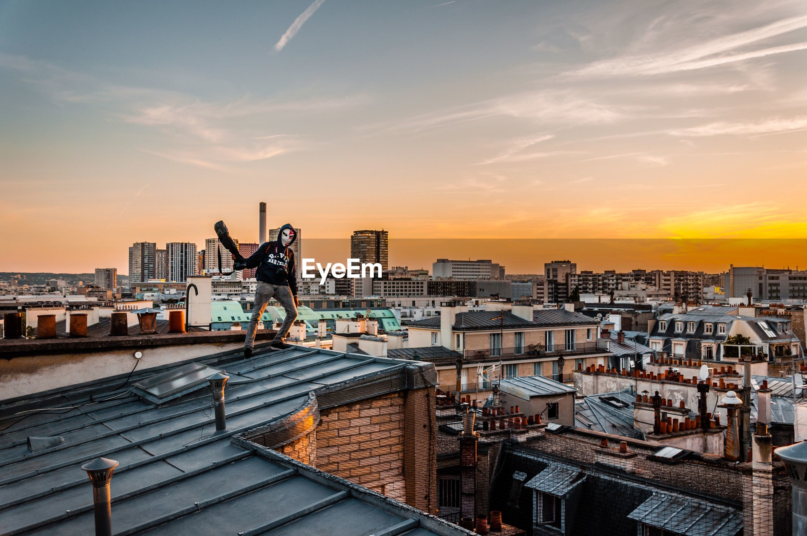 sunset, architecture, sky, city, building exterior, cityscape, built structure, orange color, nature, standing, building, residential district, crowd, one person, full length, lifestyles, real people, outdoors, leisure activity, human arm, arms raised