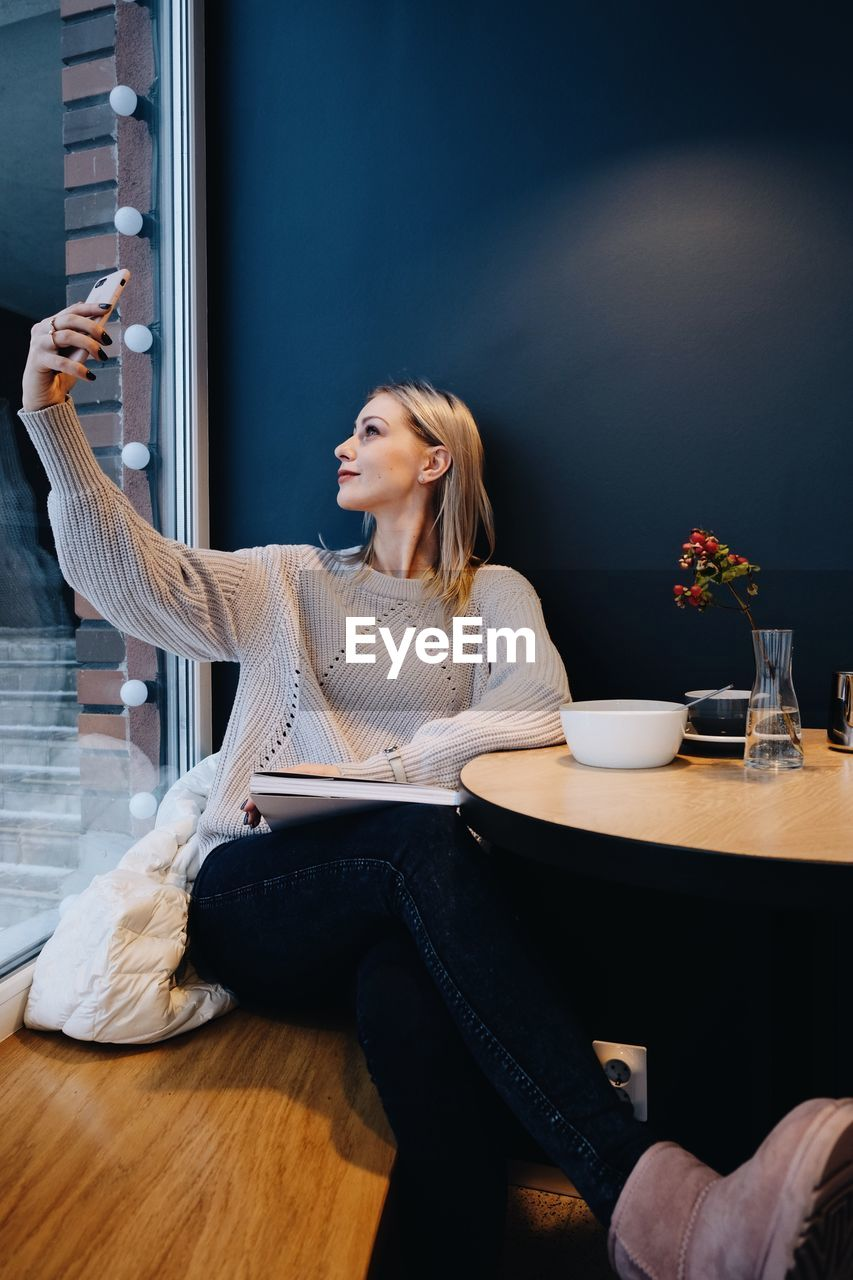 Young Woman Taking Selfie With Mobile Phone While Sitting On Table At Cafe