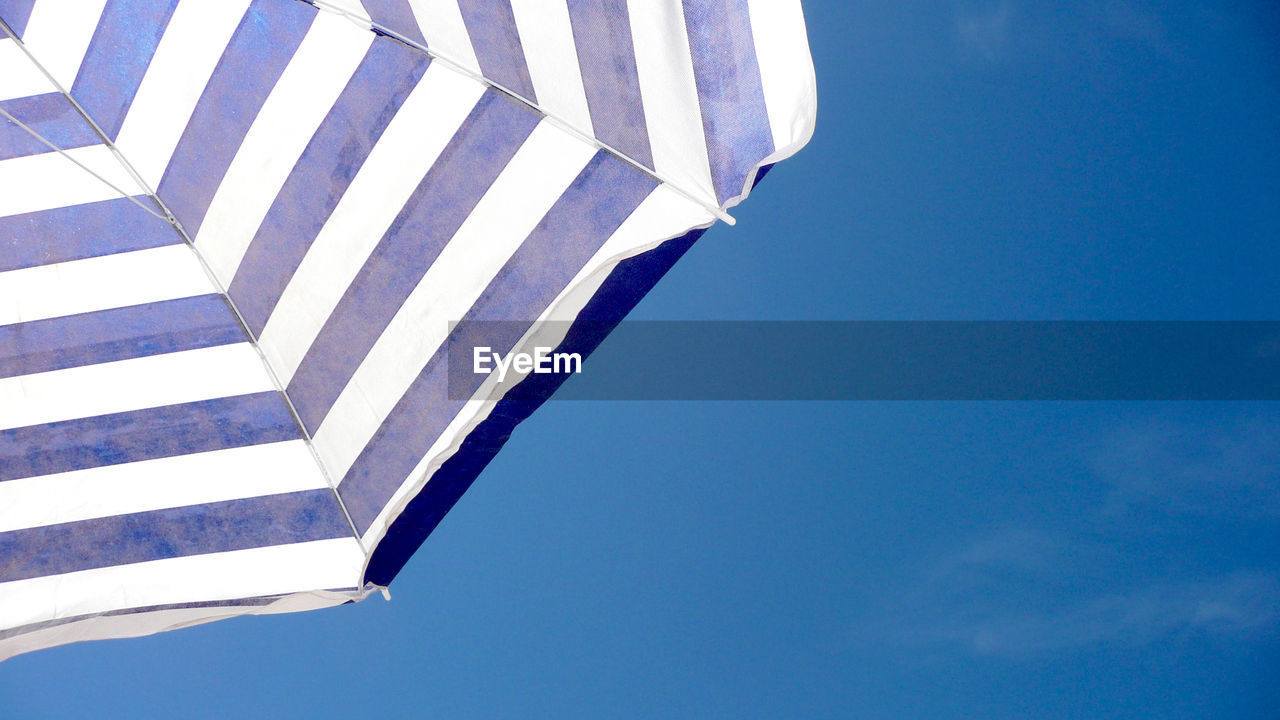 Close-Up Of Cropped Umbrella Against Clear Blue Sky