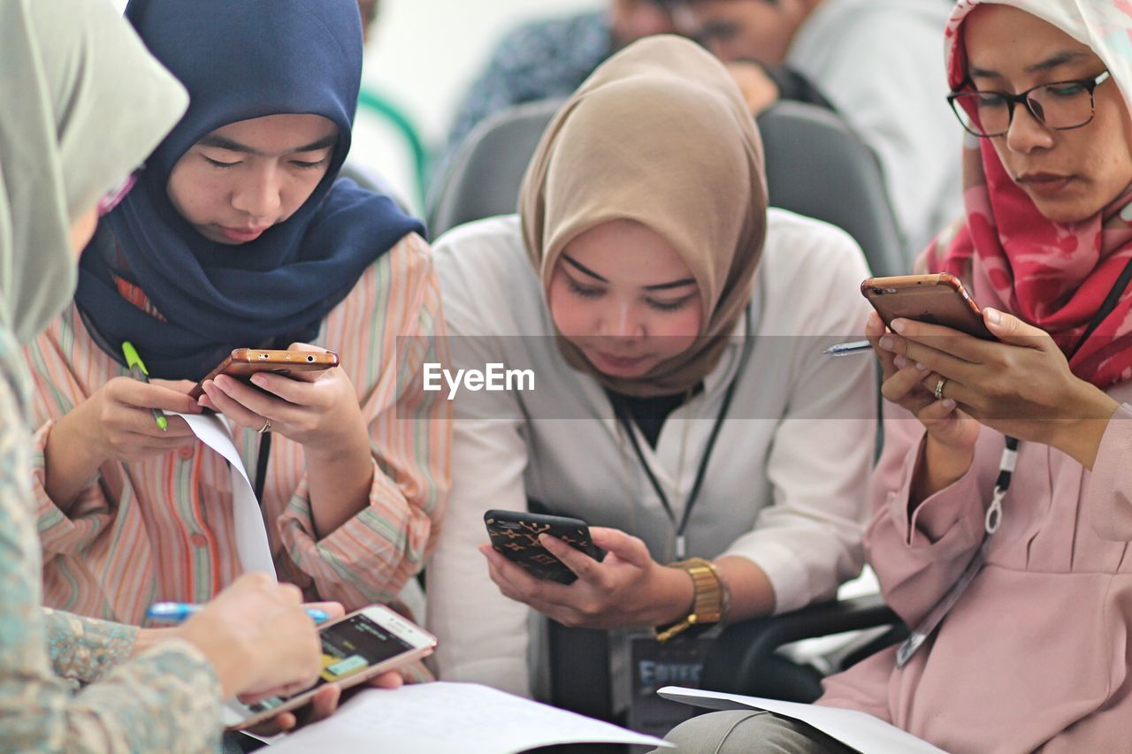 FRIENDS LOOKING AWAY WHILE USING MOBILE PHONE IN TRADITIONAL CLOTHING