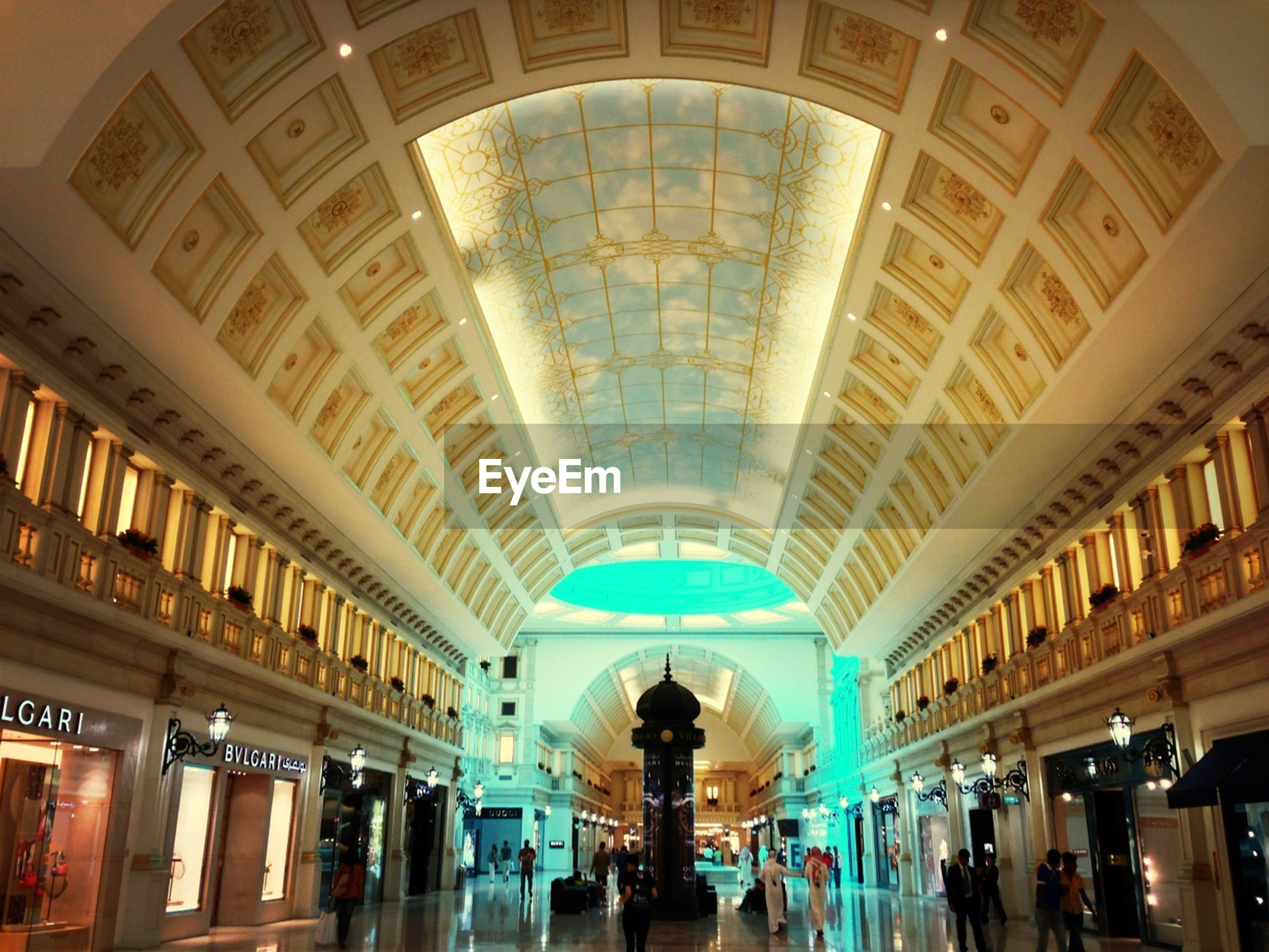 indoors, ceiling, architecture, built structure, lifestyles, large group of people, men, person, illuminated, leisure activity, arch, lighting equipment, low angle view, interior, tourist, shopping mall, travel, architectural column, tourism