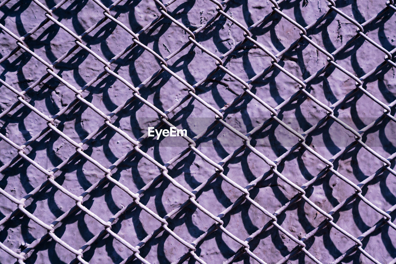 FULL FRAME SHOT OF CHAINLINK FENCE WITH METAL GRATE