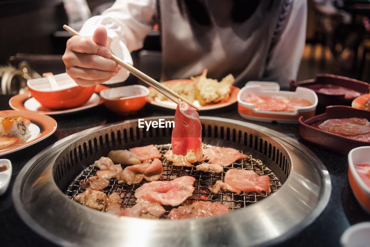 Midsection Of Woman Using Chopsticks While Picking Food From Metal Grate