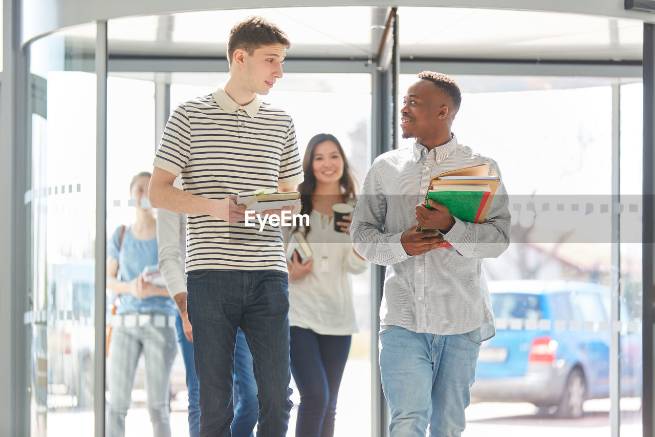 casual clothing, standing, men, indoors, young adult, three quarter length, group of people, adult, real people, day, males, young women, holding, young men, people, women, front view, togetherness, education, teenager