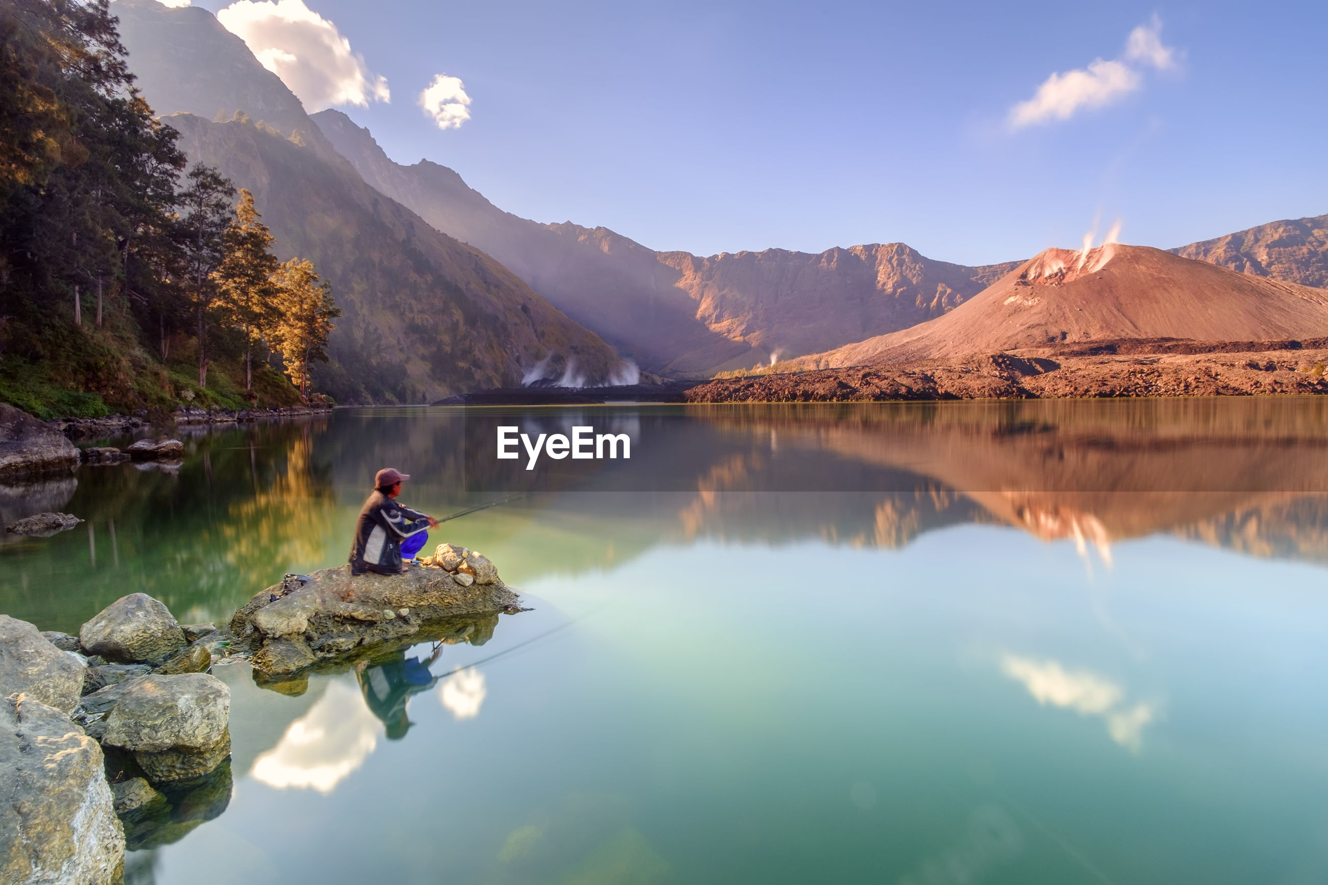 Side view of man fishing in lake while sitting on rock against sky