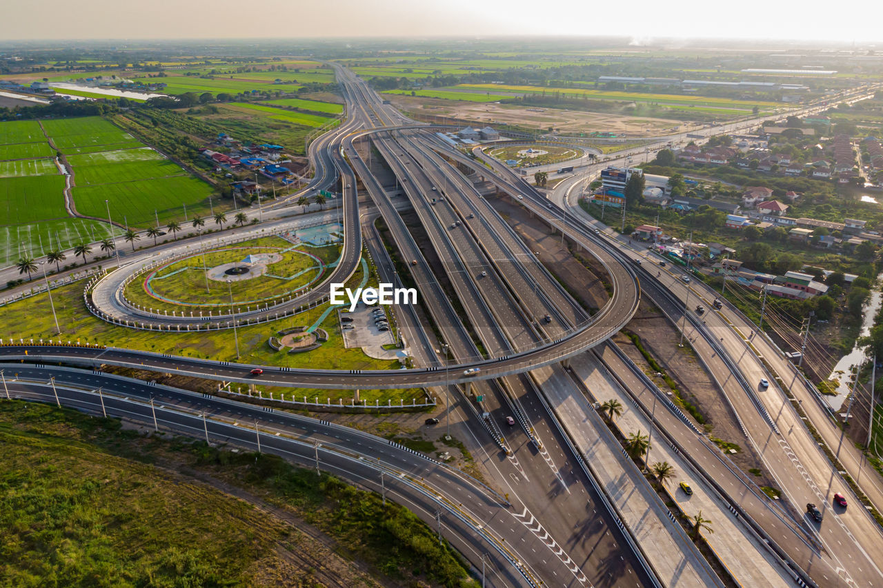 transportation, built structure, aerial view, road, city, architecture, high angle view, building exterior, mode of transportation, highway, multiple lane highway, landscape, environment, nature, no people, day, car, overpass, outdoors, sky, cityscape