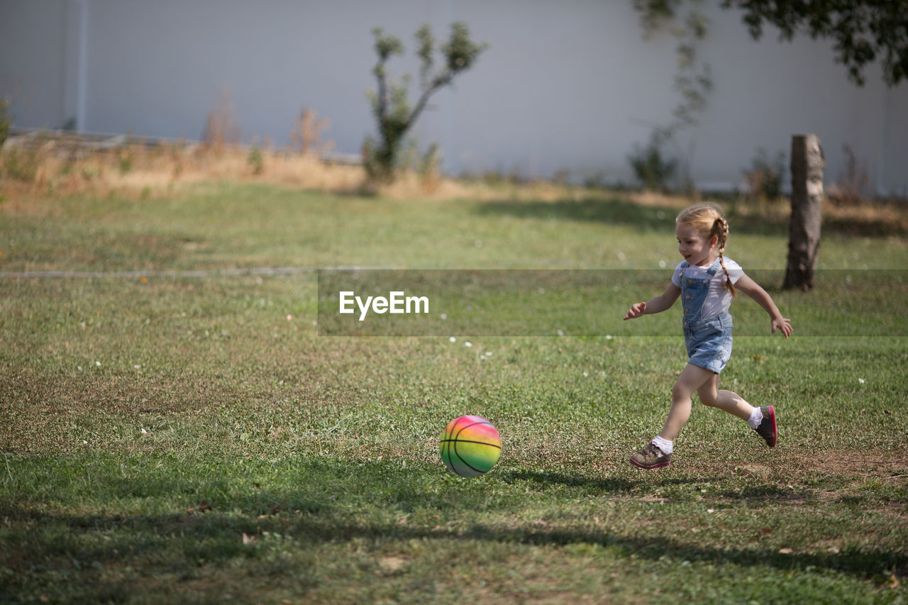 Girl Playing With Ball On Grassy Field