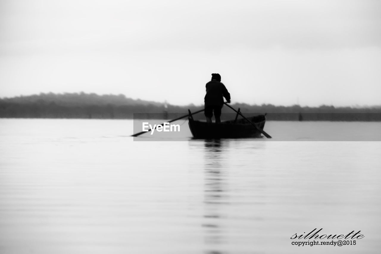 water, real people, transportation, men, oar, waterfront, one person, nature, silhouette, outdoors, tranquility, lake, nautical vessel, day, occupation, standing, beauty in nature, lifestyles, sky, rowing, adult, people