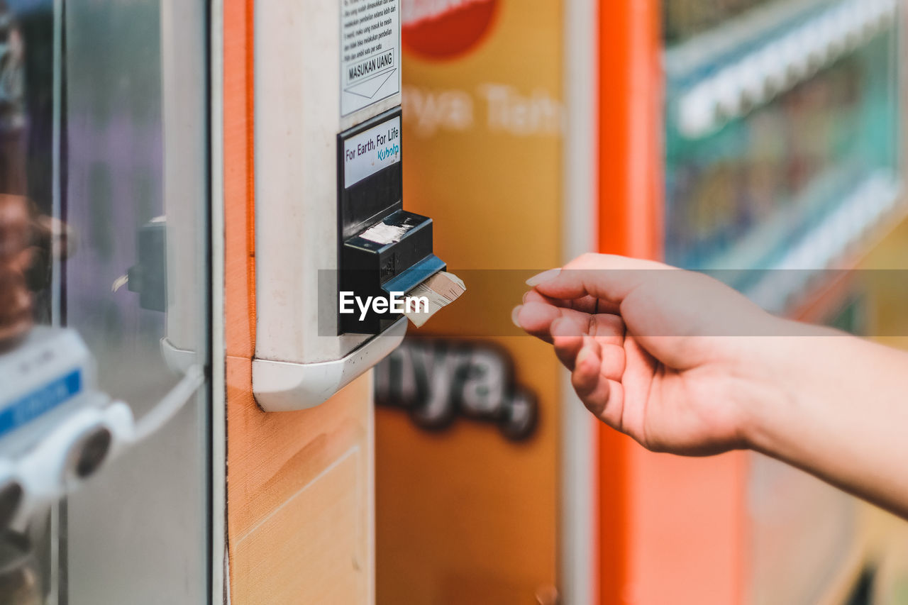 human hand, hand, human body part, real people, one person, lifestyles, holding, focus on foreground, machinery, close-up, fuel and power generation, technology, selective focus, body part, unrecognizable person, adult, finger, finance, human finger, vending machine, consumerism