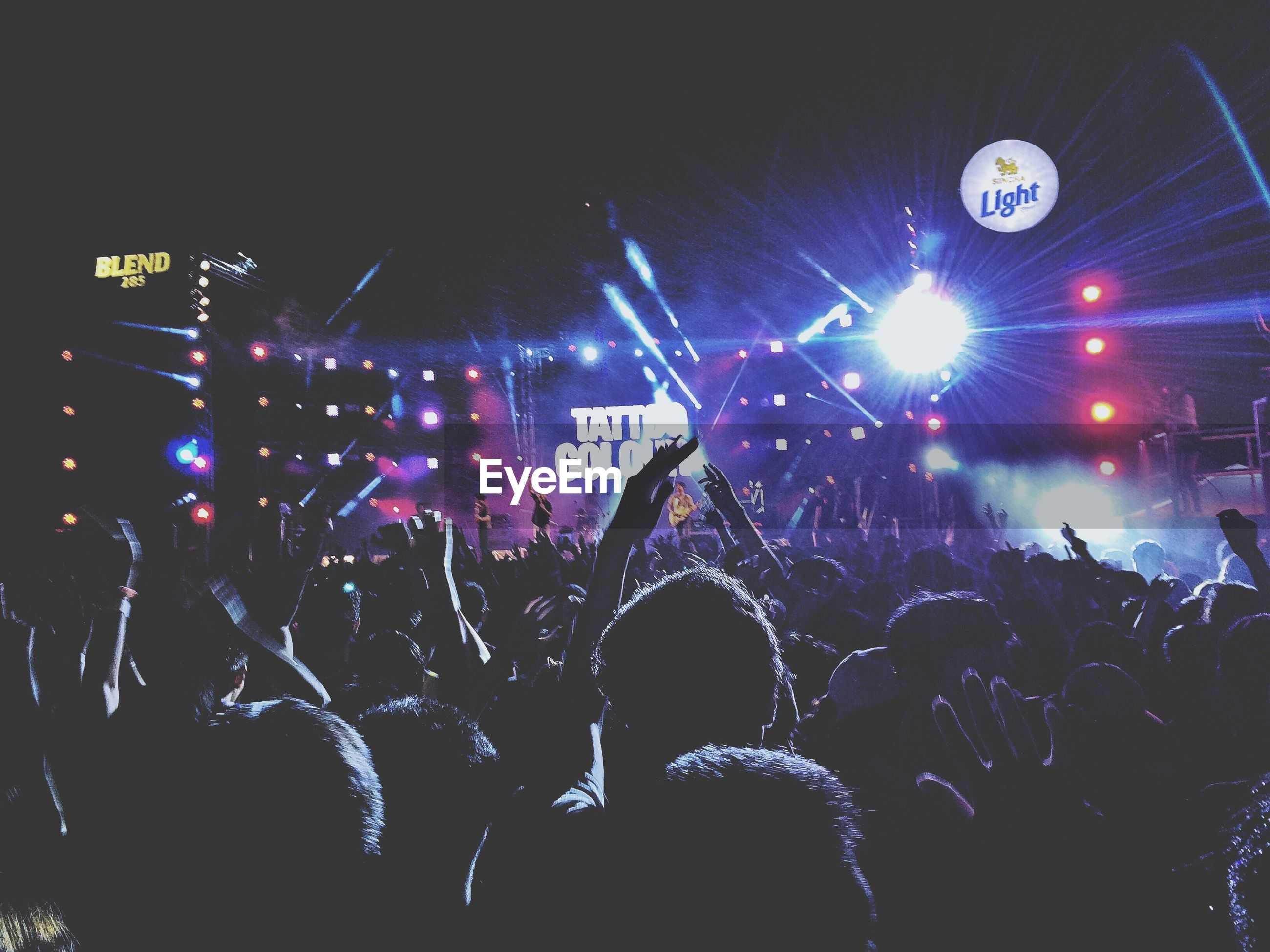 illuminated, night, large group of people, crowd, celebration, nightlife, communication, text, arts culture and entertainment, lighting equipment, performance, men, music, event, leisure activity, western script, lifestyles, person, youth culture