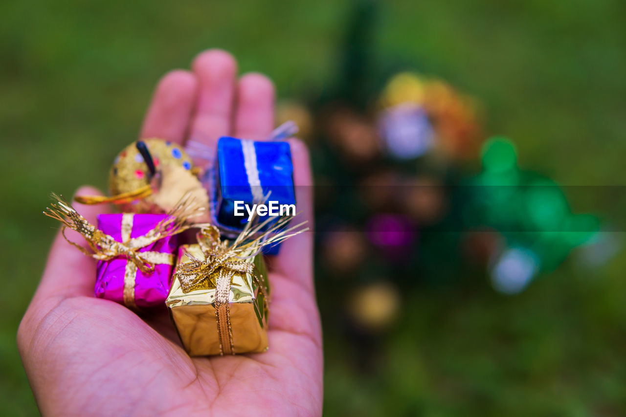 Cropped hand of person holding multi colored gifts