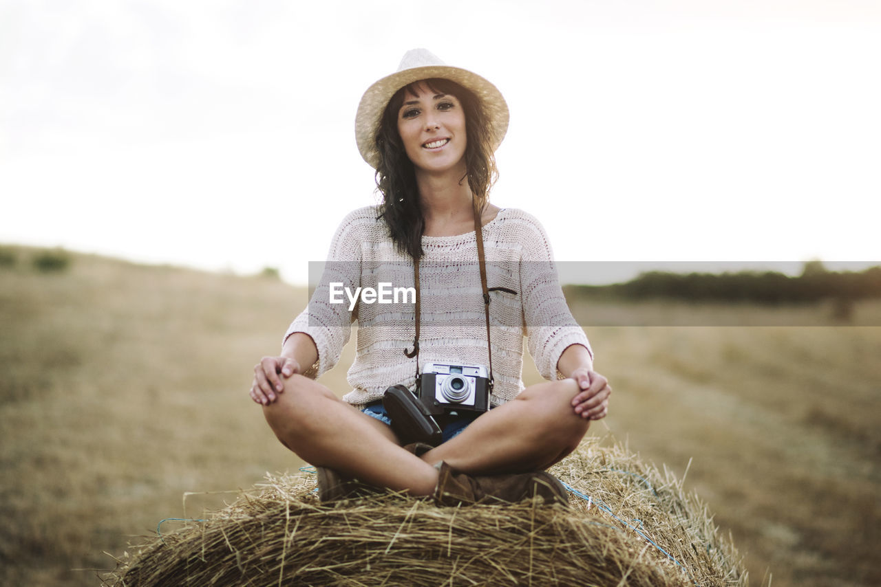 Portrait Of Woman Smiling While Sitting On Hay Bale At Field