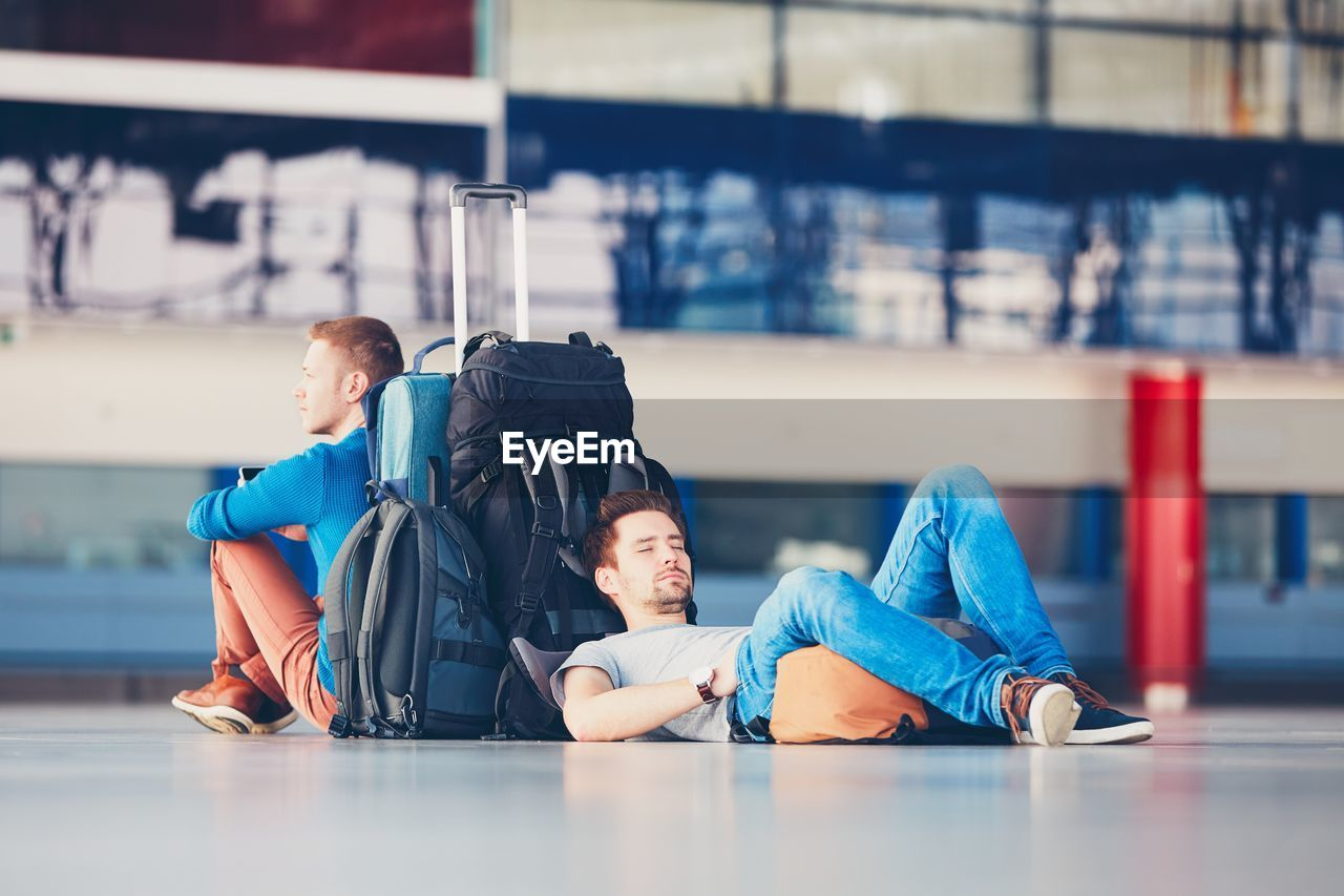 Friends with luggage waiting at airport