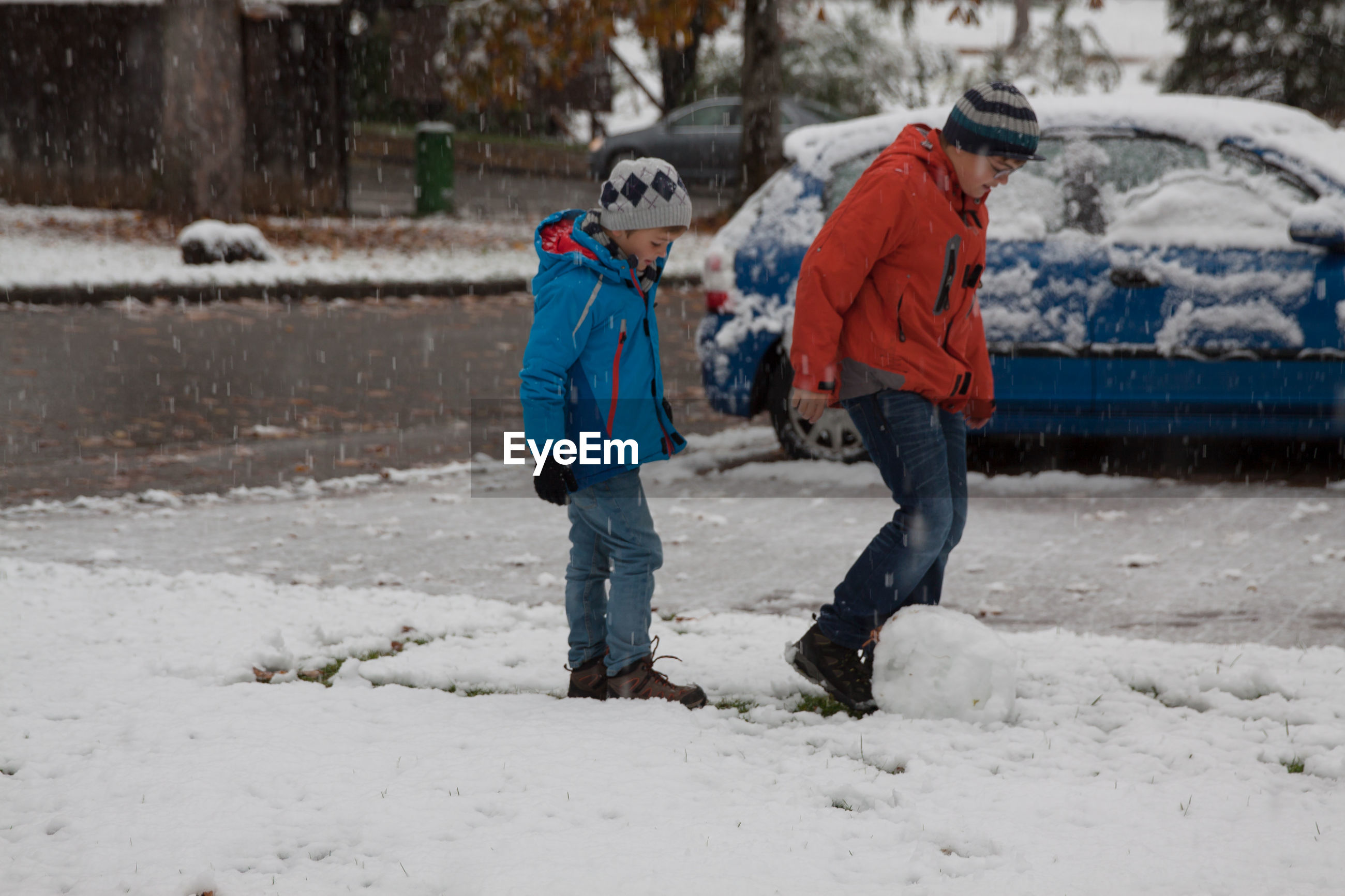 Full length of boys playing on snow covered street