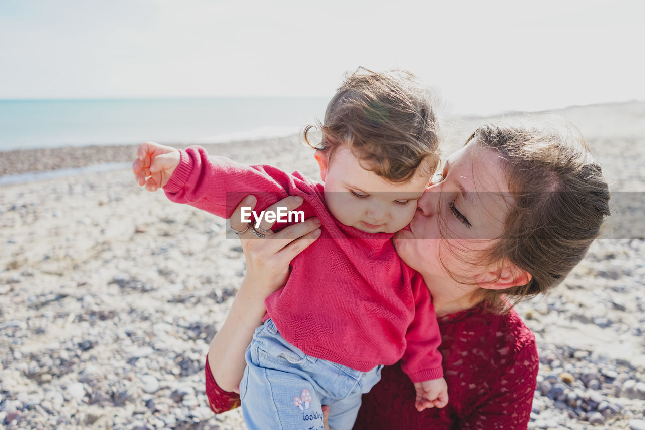 Mother kissing daughter at beach