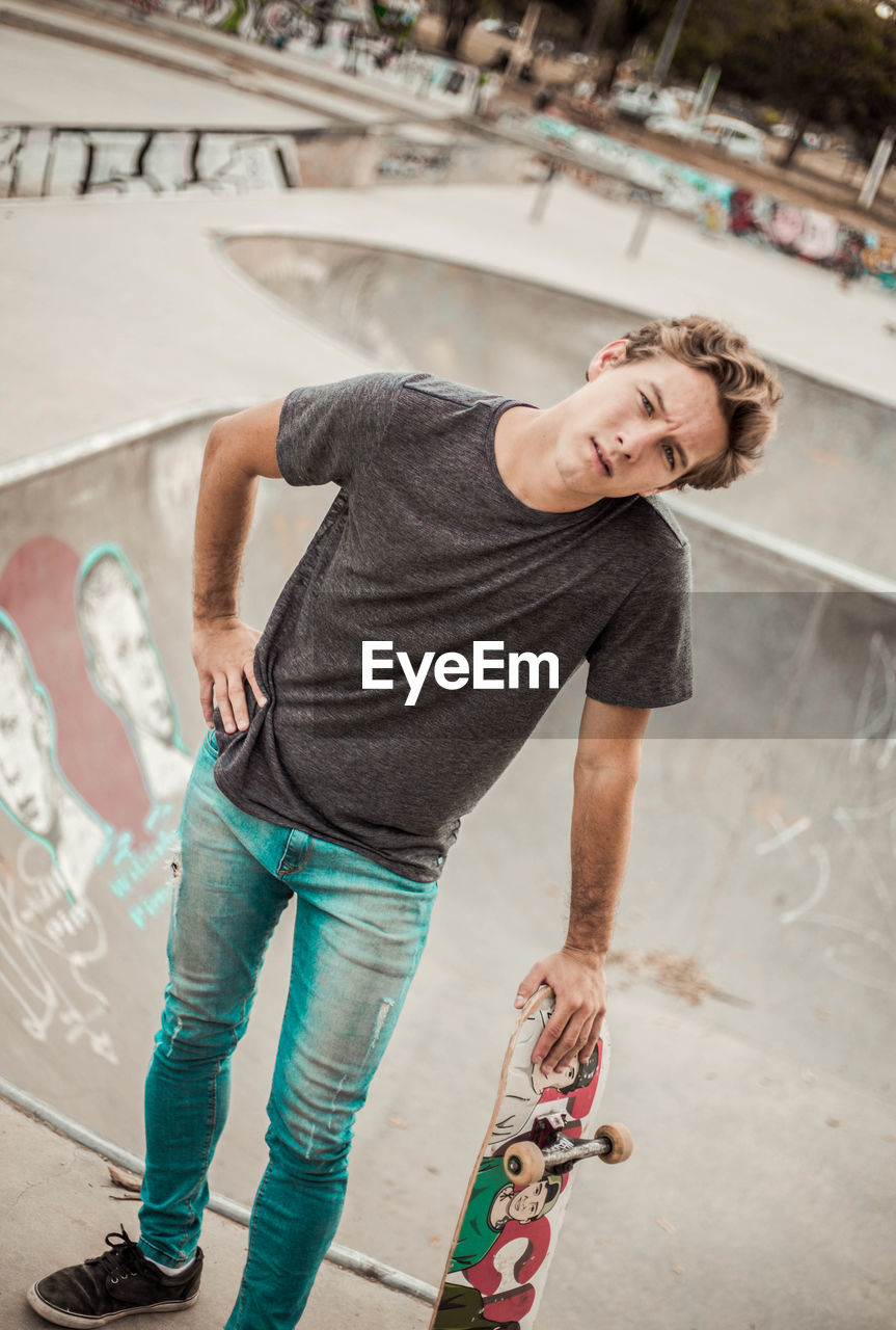 casual clothing, one person, young adult, real people, smiling, lifestyles, focus on foreground, young men, emotion, portrait, full length, indoors, happiness, graffiti, looking at camera, front view, architecture, leisure activity