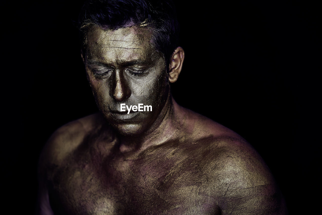Shirtless Man With Face Paint Against Black Background