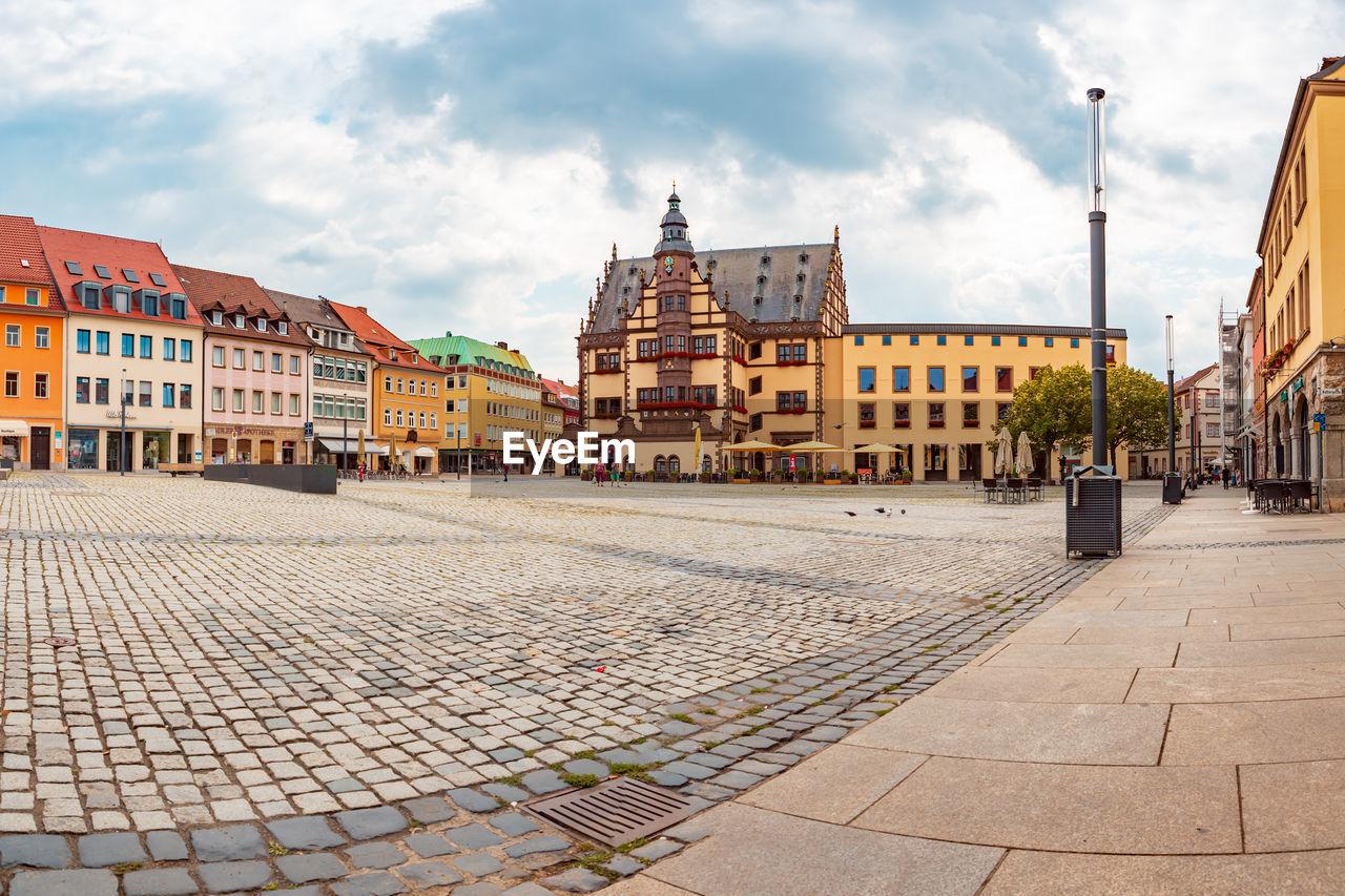 Street by buildings in town against sky