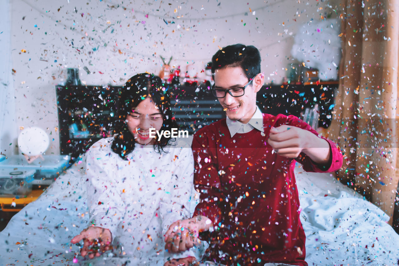 Cheerful Couple Sitting On Bed With Flying Colorful Confetti