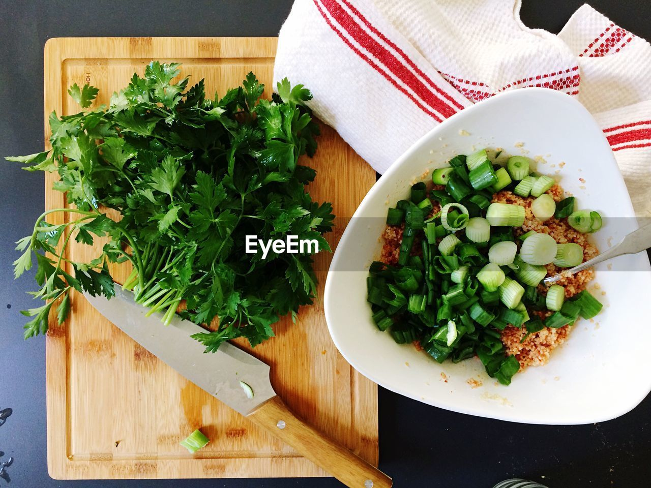 Directly Above Shot Of Food In Bowl By Cutting Board With Fresh Cilantro On Table