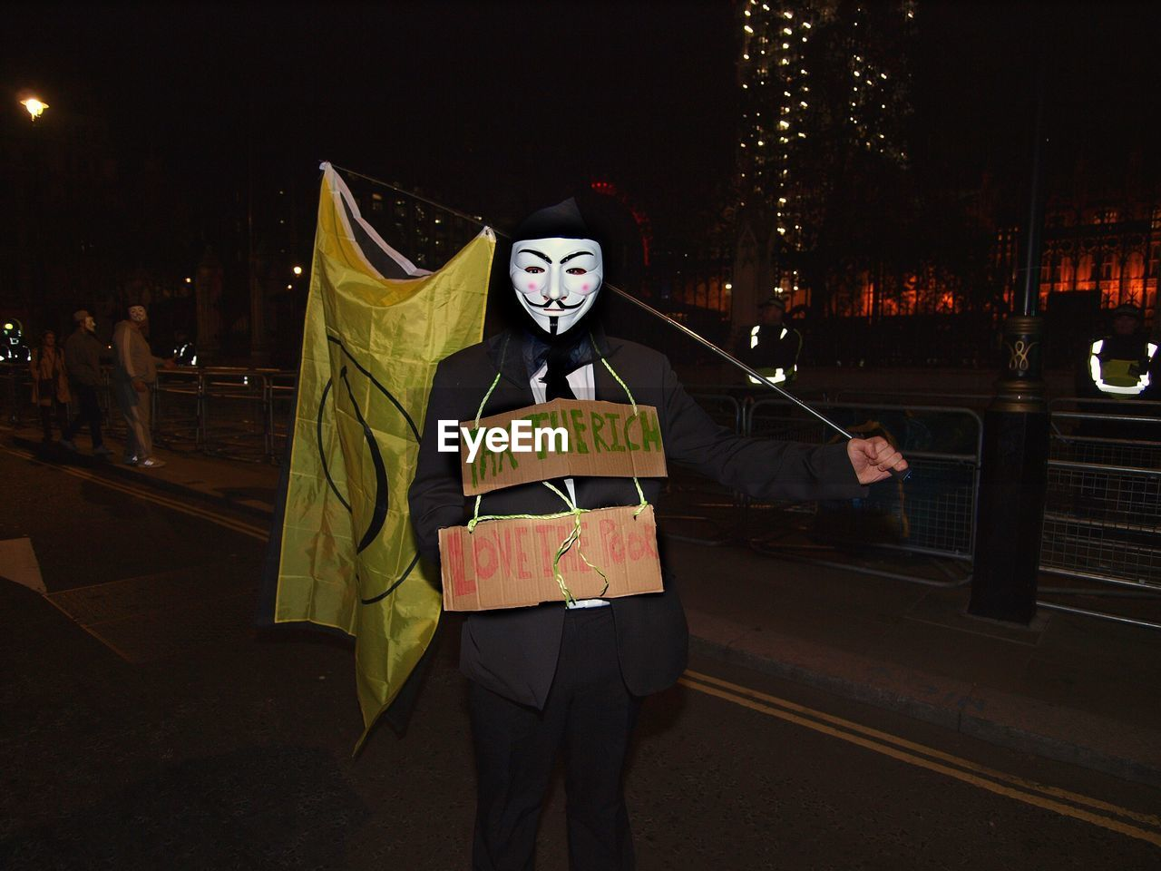 night, costume, mask - disguise, front view, illuminated, disguise, real people, outdoors, one person, men, spooky, standing, protestor, clown, people