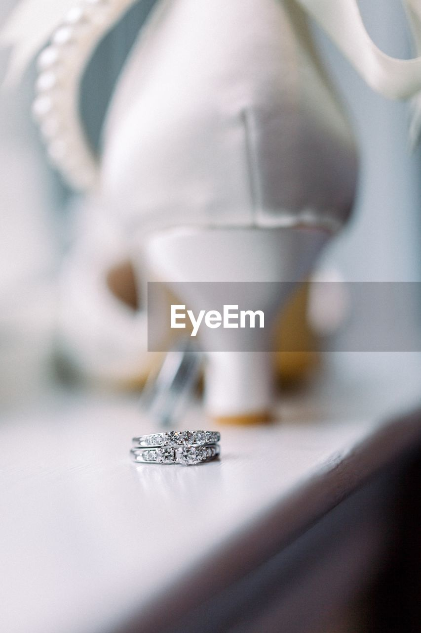 selective focus, close-up, indoors, human body part, precious gem, still life, wealth, jewelry, table, bone, expense, representation, body part, diamond - gemstone, art and craft, white color, people, luxury, royalty
