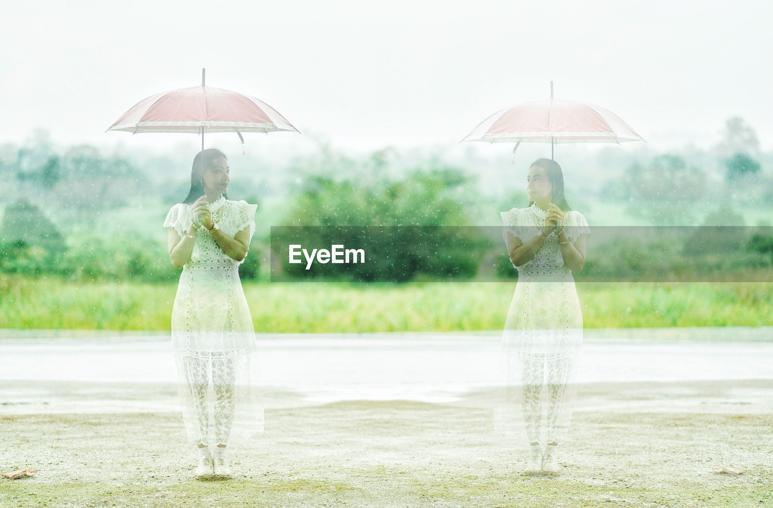 Double exposure of woman standing with umbrella in rain
