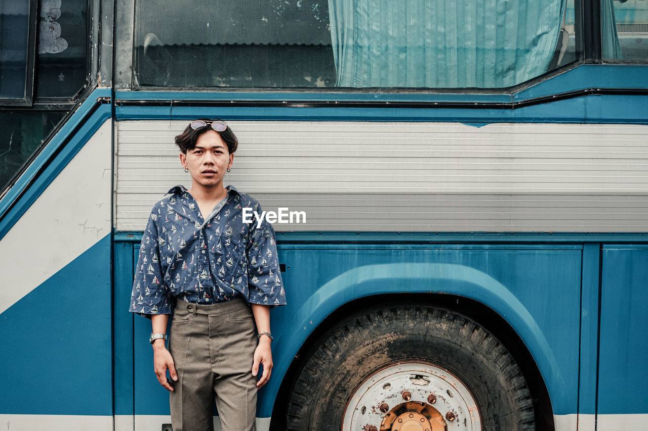 one person, real people, front view, lifestyles, three quarter length, standing, mode of transportation, casual clothing, young adult, land vehicle, day, blue, portrait, looking at camera, transportation, adult, architecture, leisure activity, outdoors