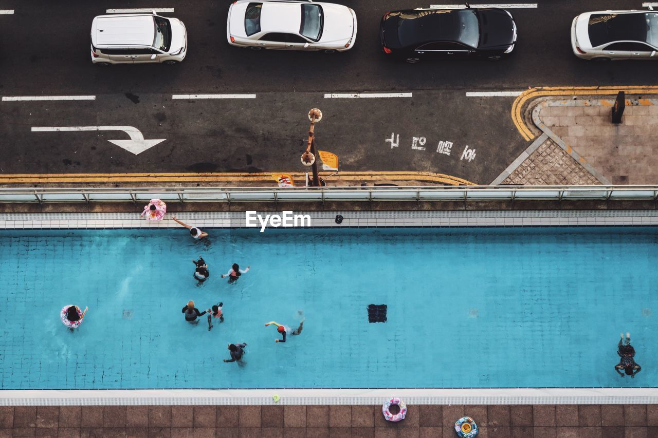 Directly Above Shot Of People In Swimming Pool By Street