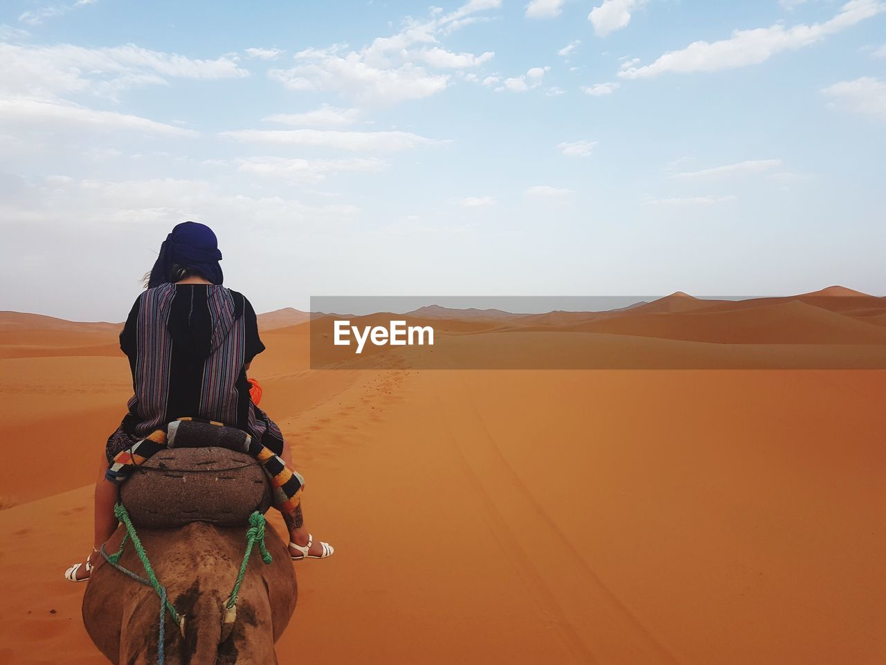 Rear View Of Woman Riding Camel At Desert Against Sky