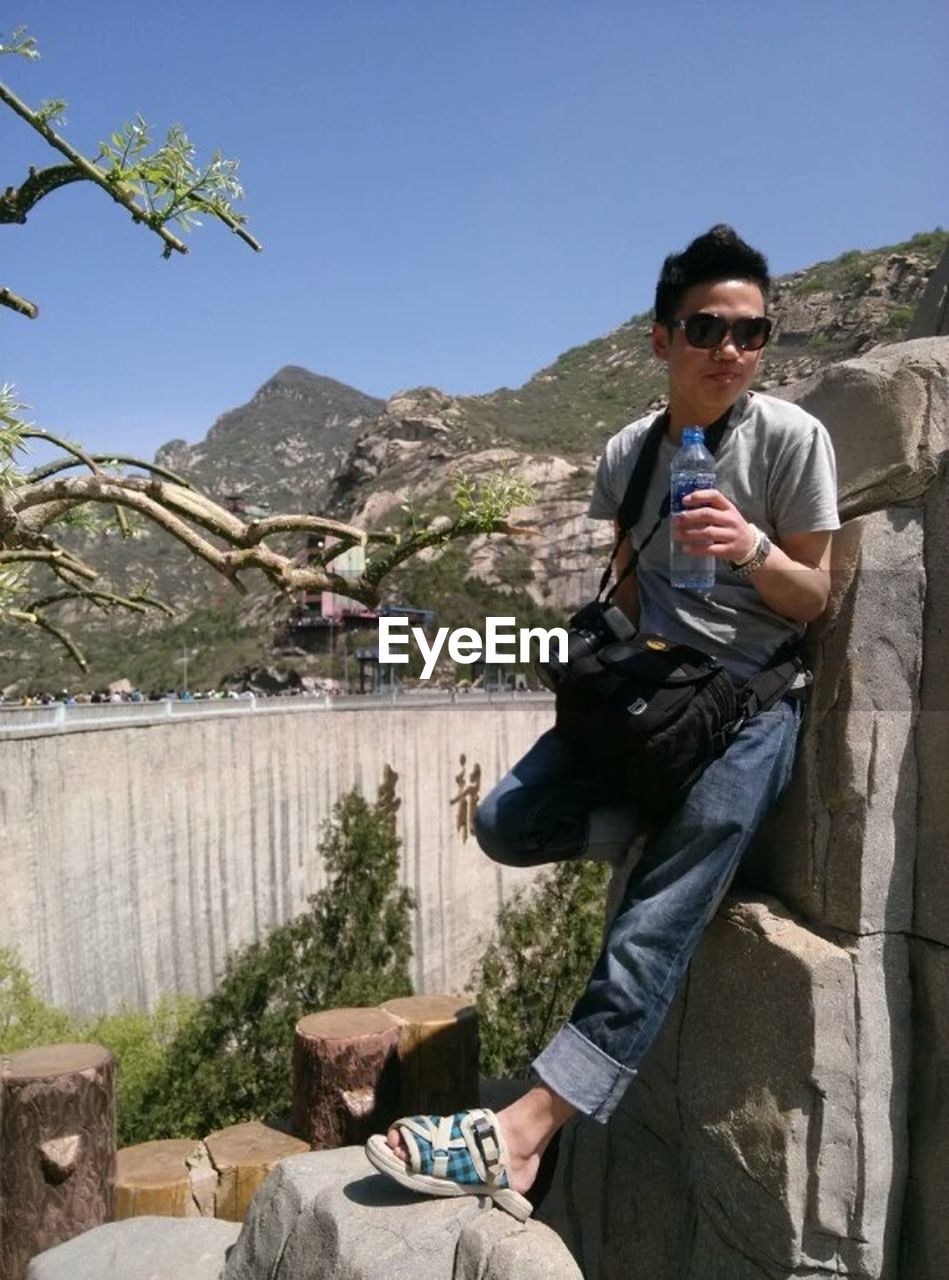mountain, sunglasses, young adult, outdoors, one person, day, three quarter length, standing, rock - object, young men, holding, front view, wireless technology, technology, smiling, looking at camera, men, mountain range, nature, leisure activity, lifestyles, one man only, mobile phone, communication, portrait, real people, vacations, clear sky, only men, sky, adults only, one young man only, scenics, adult, beauty in nature, architecture, people