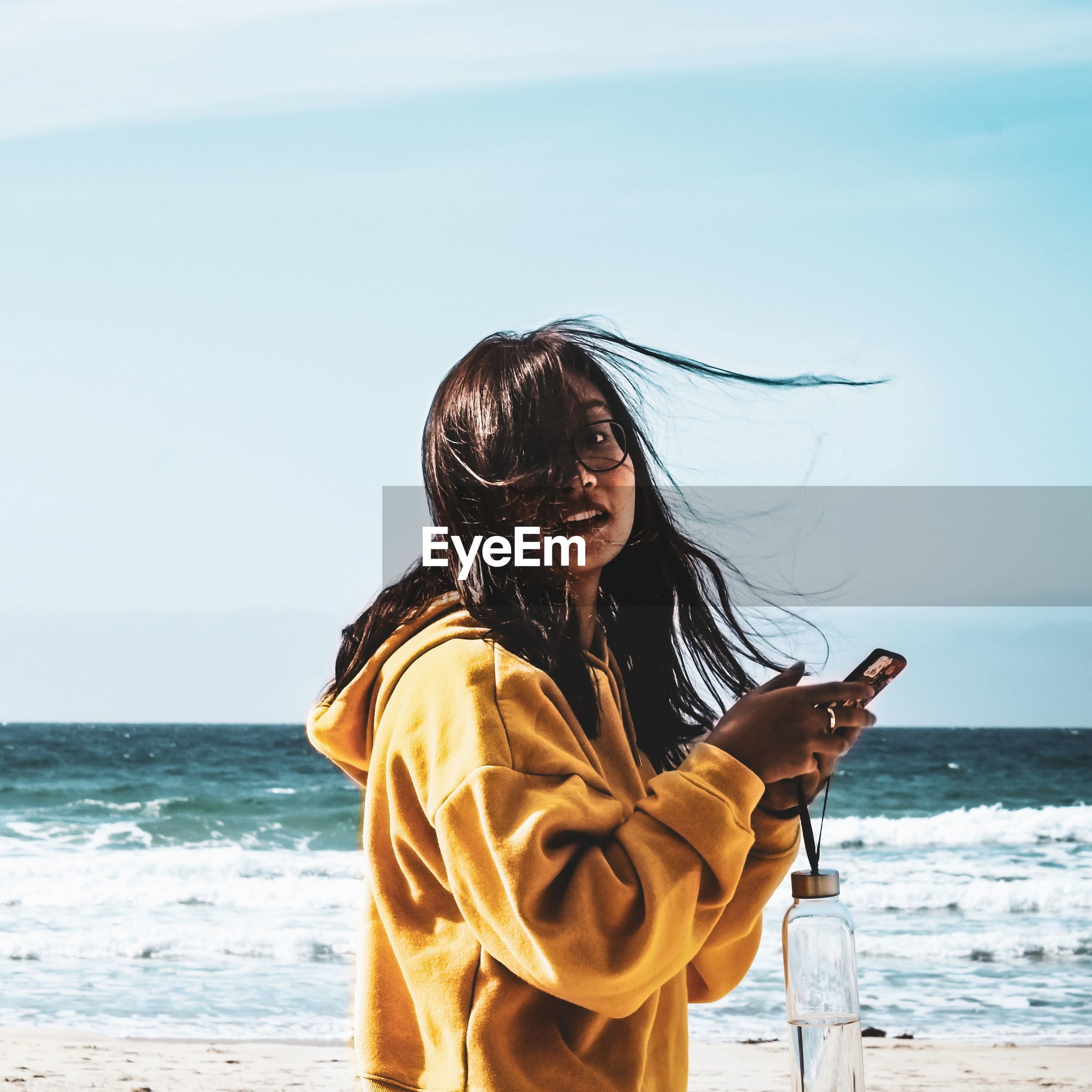 Portrait of woman with tousled hair using phone while standing at beach against sky