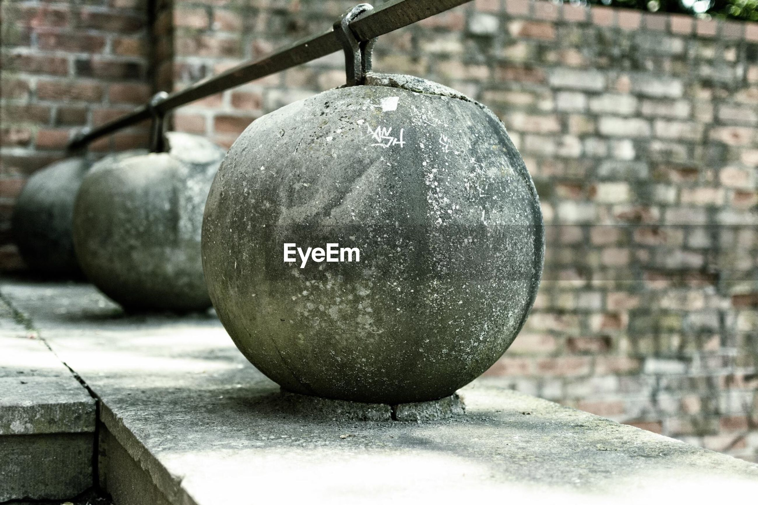 close-up, focus on foreground, metal, still life, day, hanging, built structure, outdoors, no people, sphere, fruit, wall - building feature, sunlight, architecture, metallic, old, container, stone - object, stack
