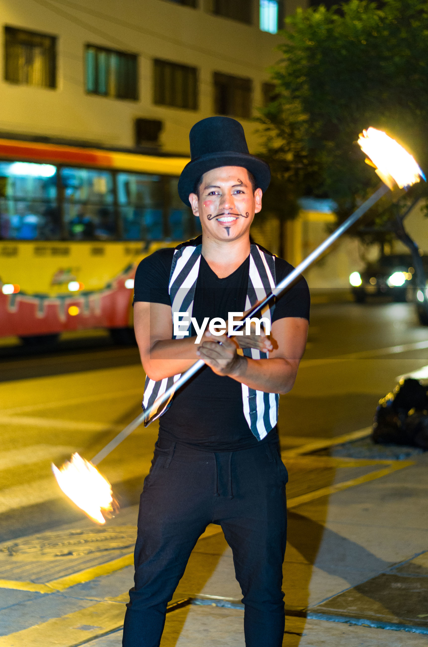 Portrait of cheerful man performing with fire on street at night