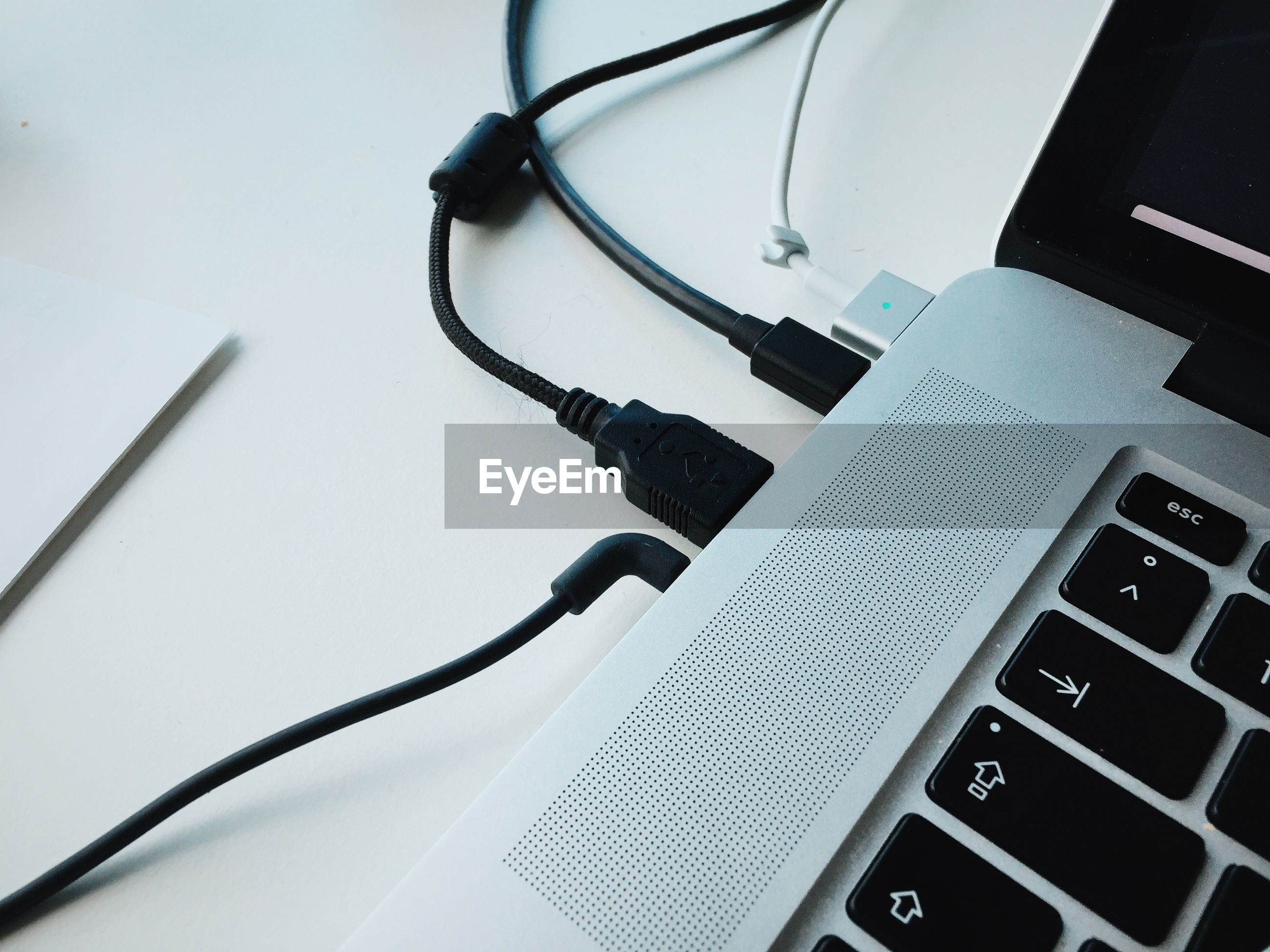 Close-up of usb cables attached to laptop on table