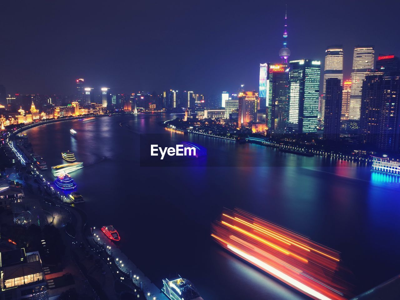 illuminated, city, night, skyscraper, architecture, building exterior, cityscape, built structure, urban skyline, travel destinations, modern, city life, tower, downtown district, outdoors, financial district, light trail, no people, urban scene, tall, clear sky, water, sky
