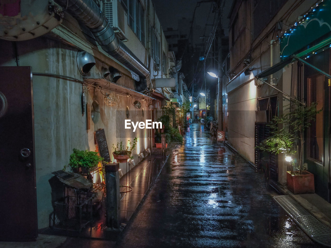 ILLUMINATED ALLEY AMIDST BUILDINGS IN CITY AT NIGHT