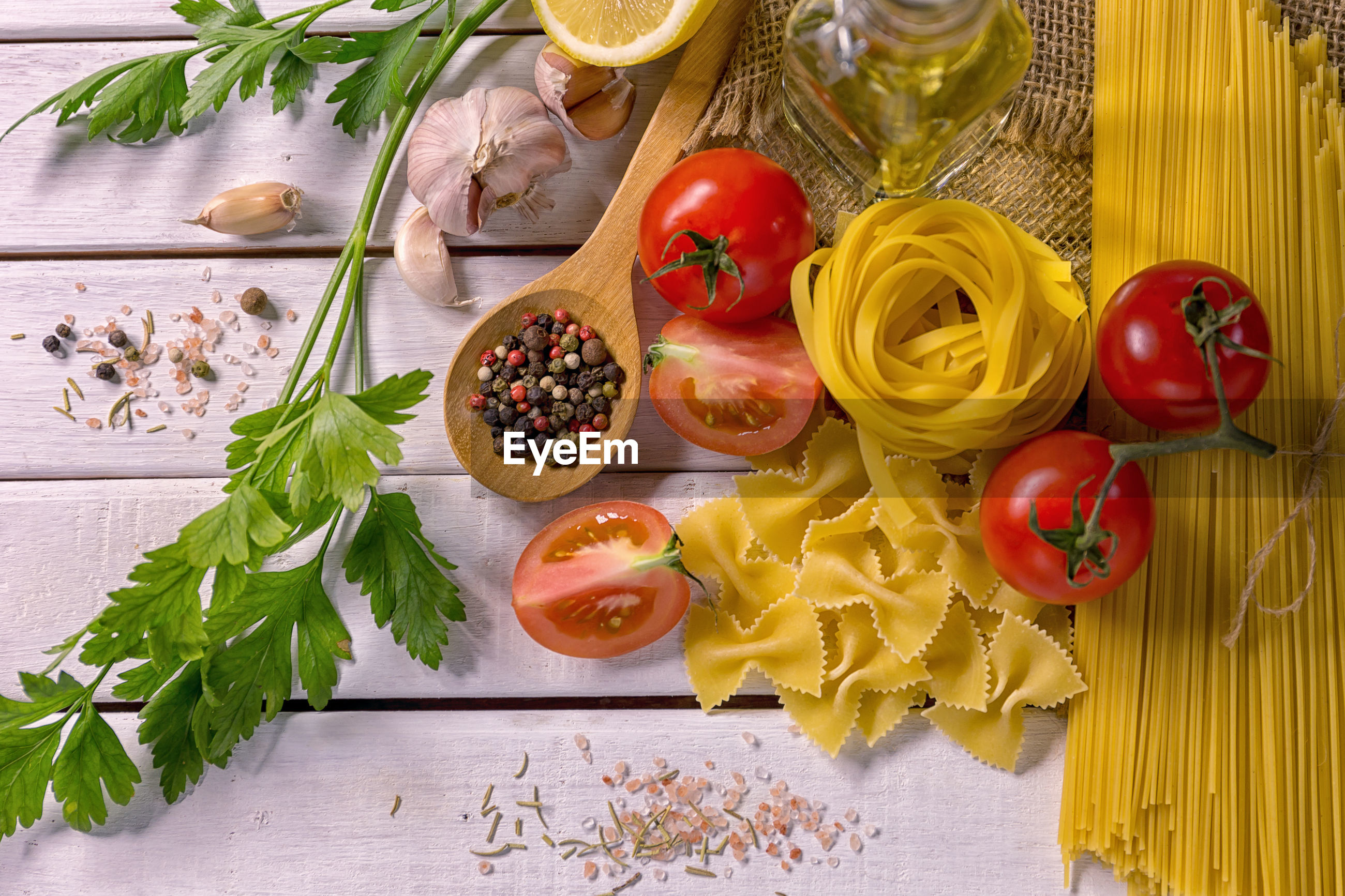 High angle view of raw pasta and vegetables on table