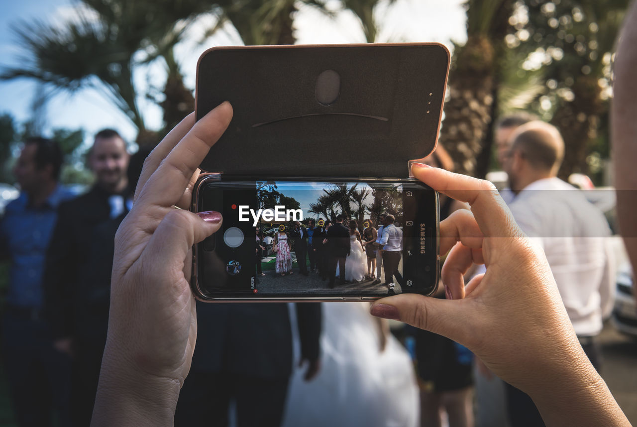 photography themes, technology, real people, wireless technology, photographing, human hand, smart phone, portable information device, holding, communication, screen, lifestyles, activity, mobile phone, hand, group of people, focus on foreground, leisure activity, people, adult, outdoors