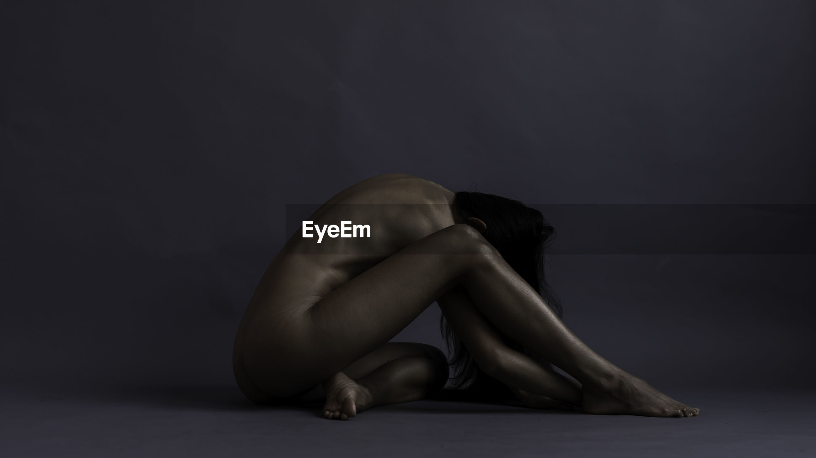 Full length of naked woman sitting against gray background