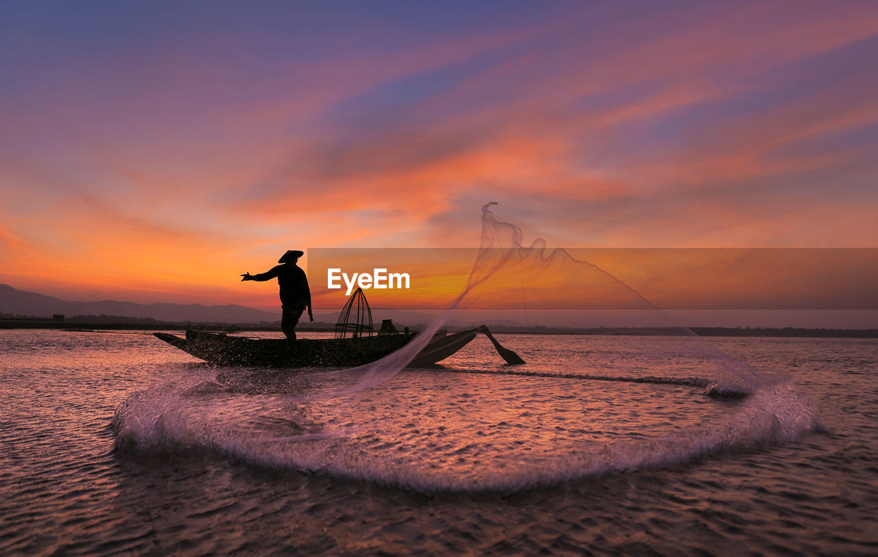 sunset, sky, water, sea, real people, silhouette, beauty in nature, scenics - nature, one person, horizon over water, men, orange color, nautical vessel, cloud - sky, waterfront, horizon, standing, idyllic, fisherman, outdoors, fishing industry