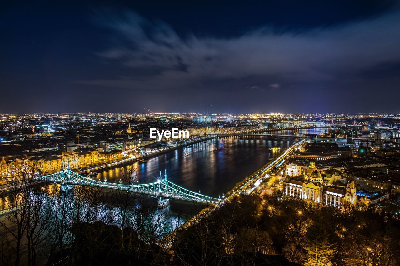 architecture, built structure, building exterior, sky, cityscape, bridge - man made structure, connection, city, residential district, cloud - sky, illuminated, chain bridge, no people, suspension bridge, night, river, travel destinations, outdoors, residential building, water, nature
