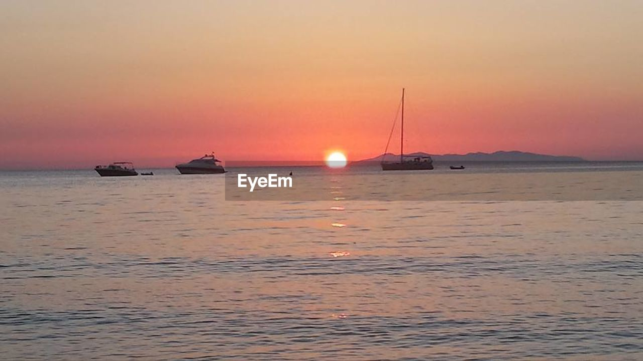 sunset, sun, sea, nautical vessel, dramatic sky, horizon over water, scenics, landscape, nature, beauty in nature, travel destinations, dusk, no people, travel, tranquility, sky, cloud - sky, transportation, beach, tranquil scene, outdoors, sailboat, sunlight, vacations, water, red, yacht