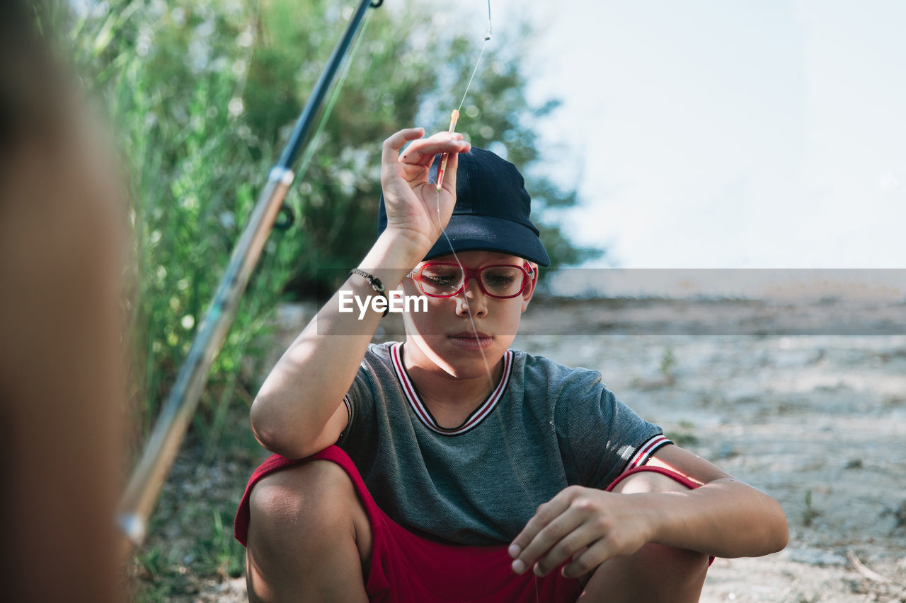 Boy Holding Fishing Rod While Crouching On Field