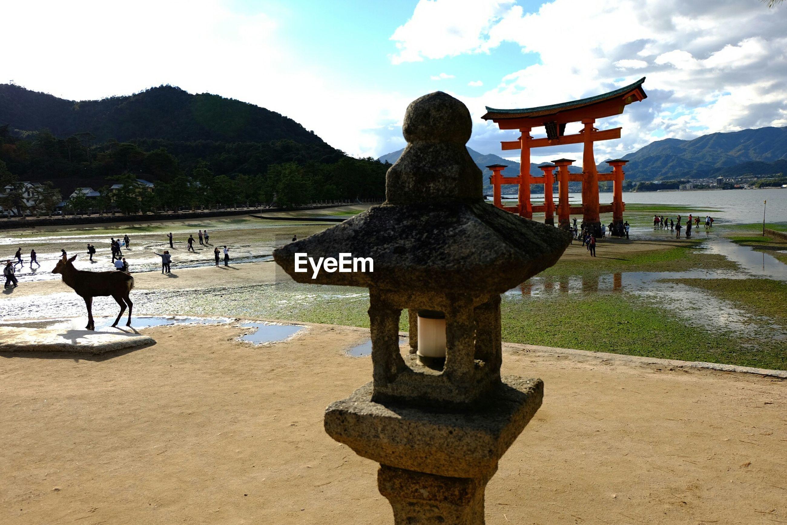 Stone lantern by itsukushima shrine against sky