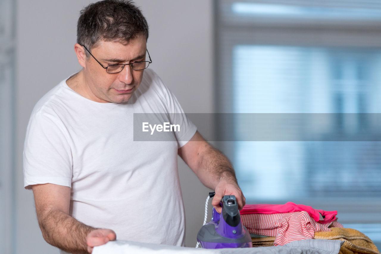 Man ironing cloth at home