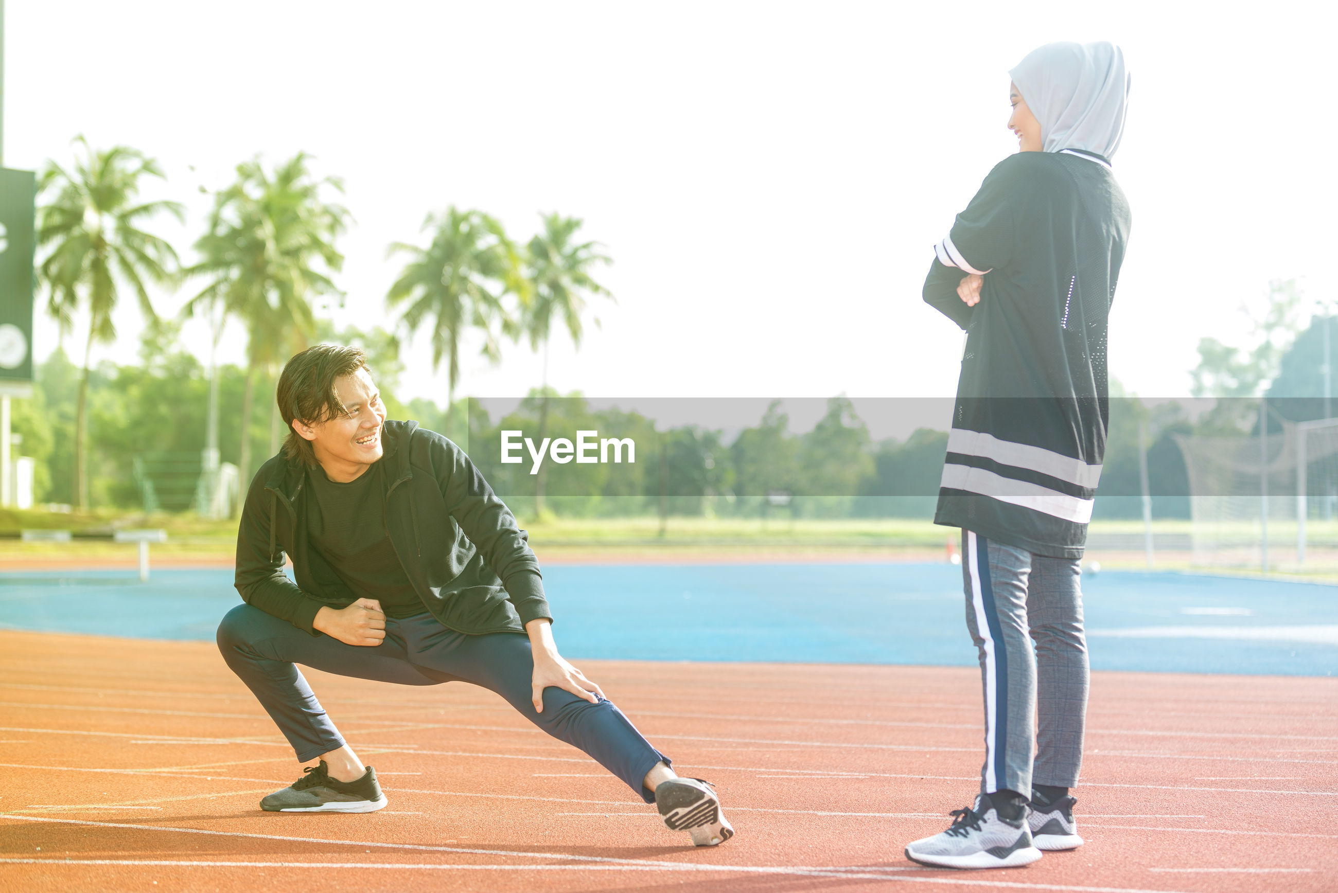 Young woman looking at friend stretching while standing on running track