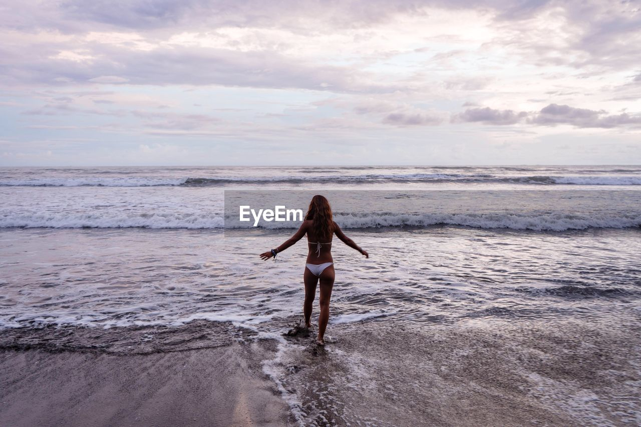 Rear view of carefree woman walking towards sea on shore at beach against cloudy sky