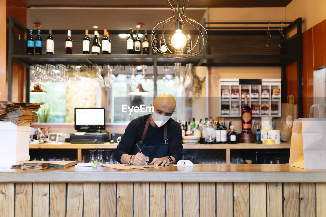 MAN WORKING ON TABLE AT BAR